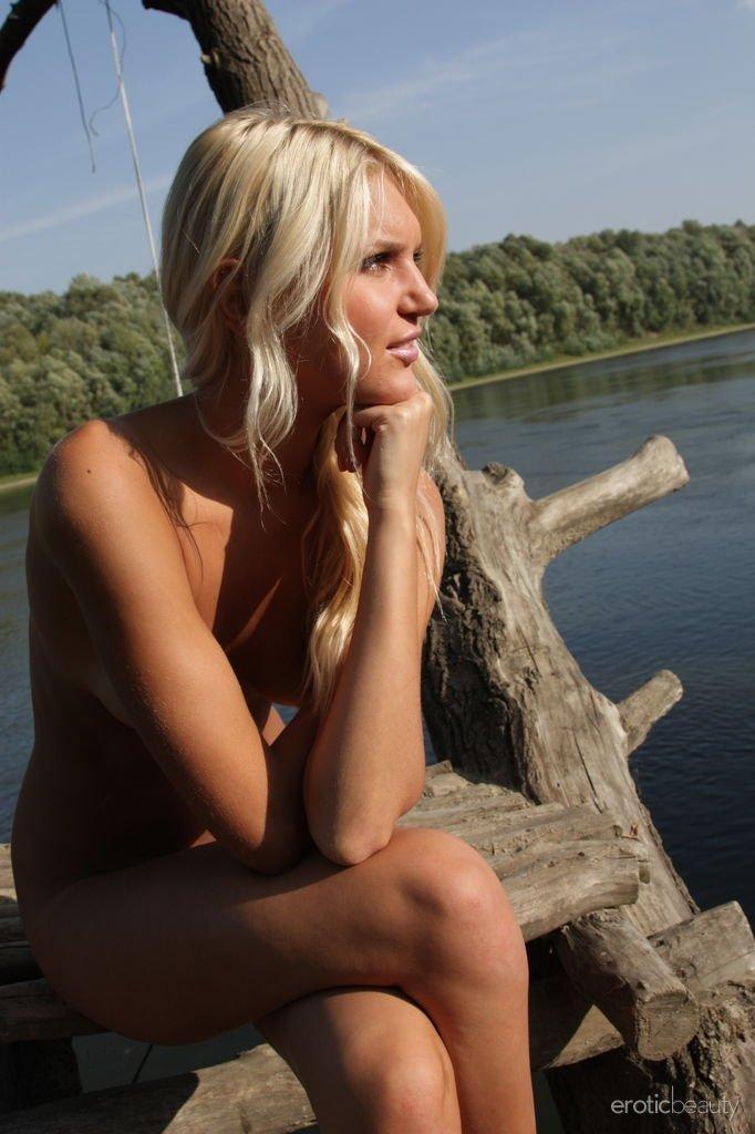 Стройная блондинка загорает голой на речке в деревне