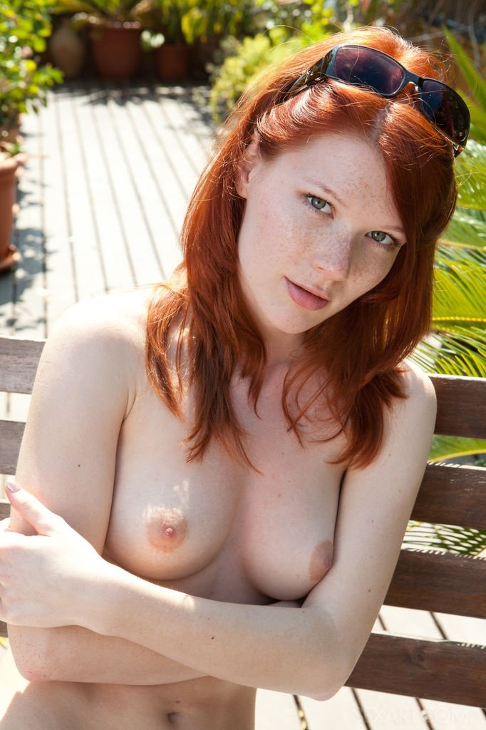 Рыжая девушка снимает купальник на лавочке и засовывает пальцы в киску