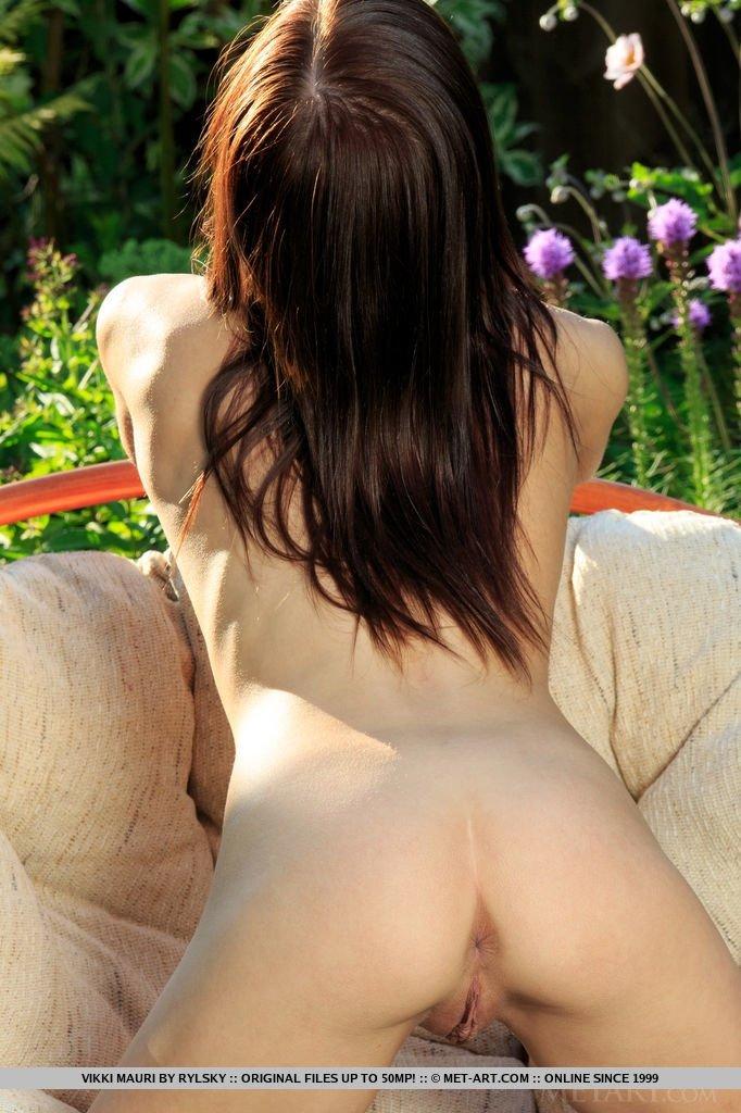 Красивая девушка показывает пизду в саду на мягком кресле