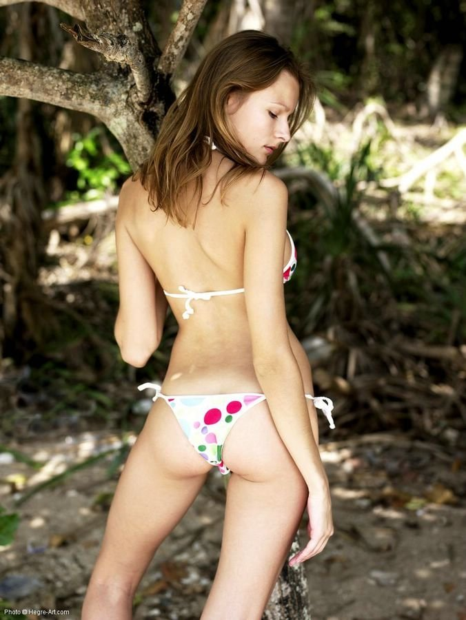Стройная девушка снимает бикини в лесу