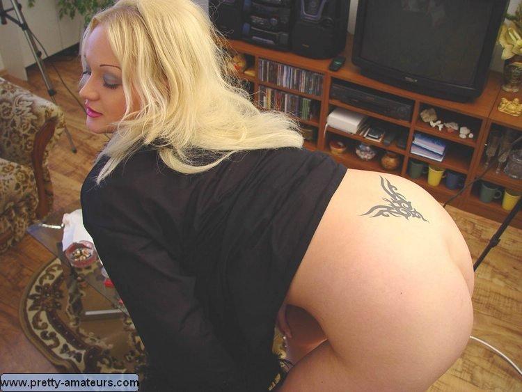 Пухлая блондинка с хорошей фигурой показывает тату на пояснице