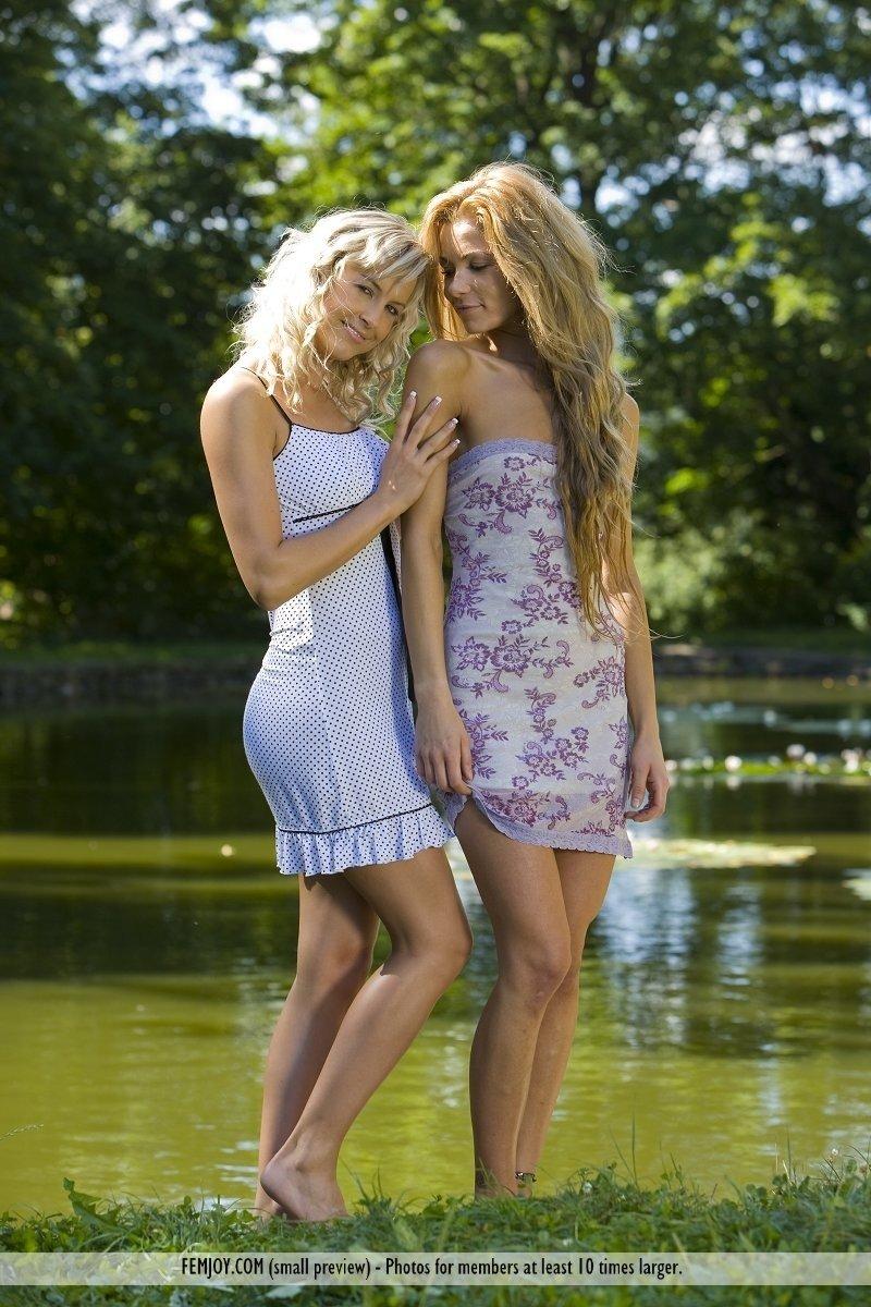 Две голые подружки обнимаются у пруда