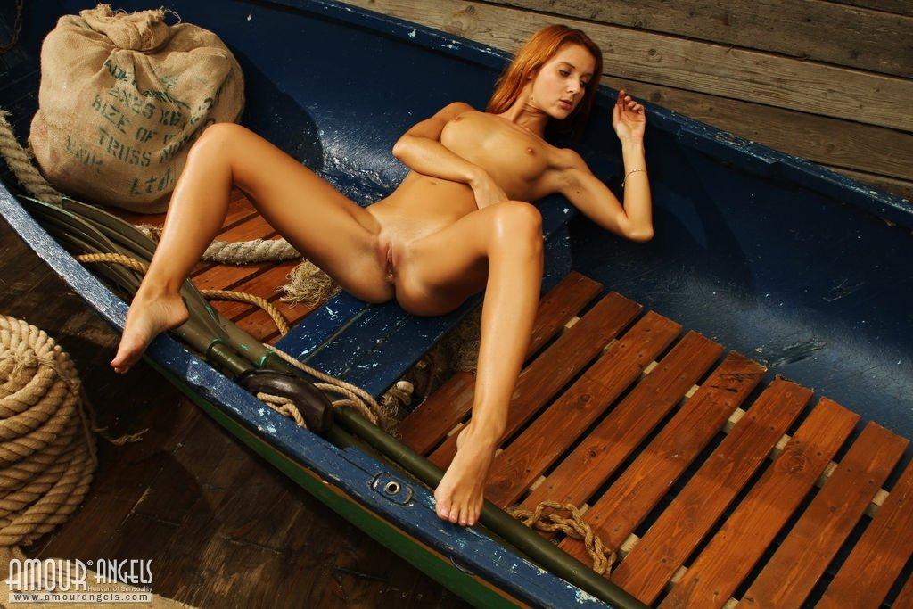 Рыжая девушка с бритой киской раздвигает красивые ножки