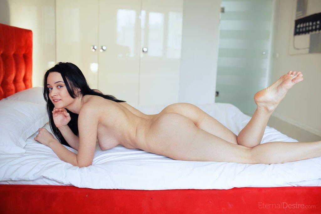 Брюнетка с красивой, гладкой пиздой лежит в кровати одна