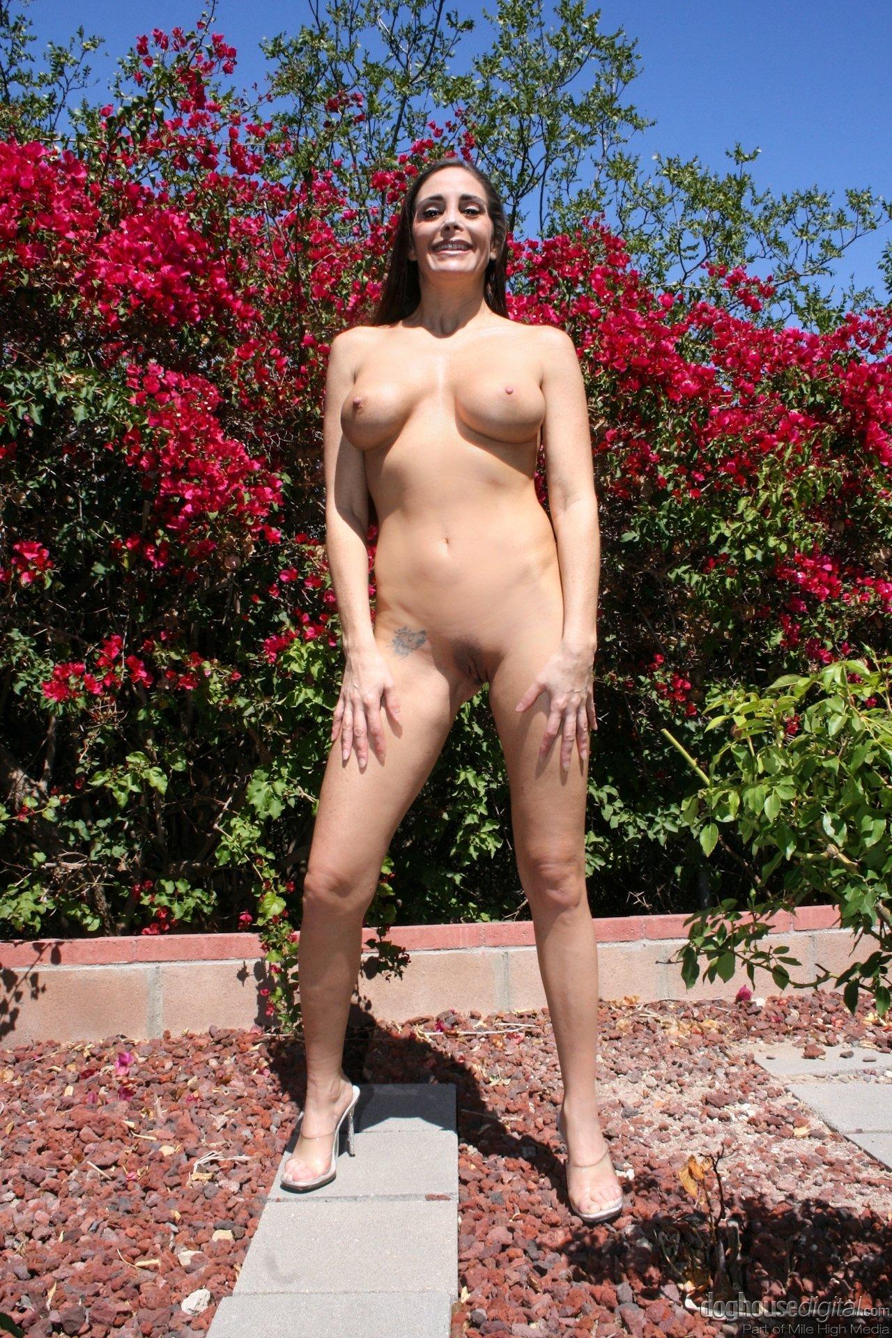 Красивая женщина обнажилась на фоне красного кустарника
