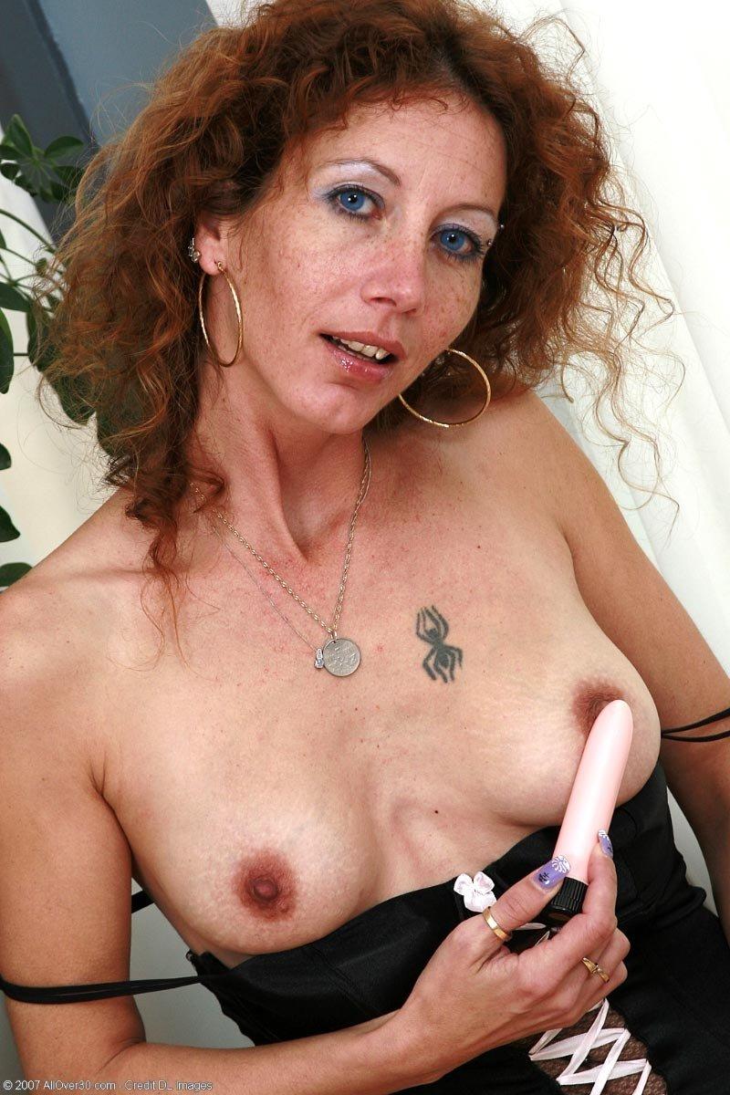 Рыжая женщина с едва заметной грудью занимается мастурбацией