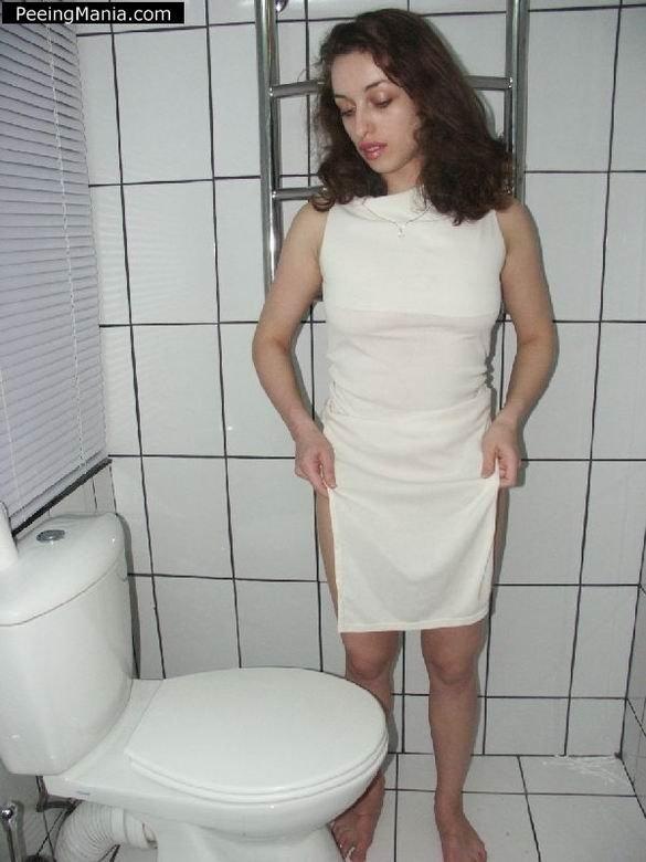 Красивая женщина писает стоя над унитазом