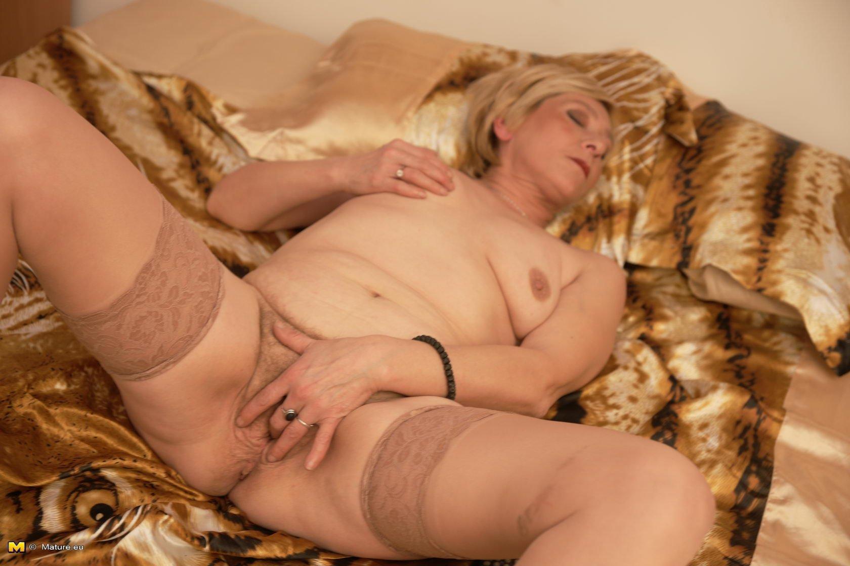 Коротковолосая пожилая блондинка ласкает свою старую волосатую пизду