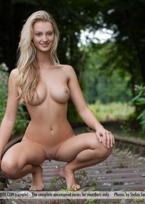 Голая блондинка на заброшенной железной дороге в лесу