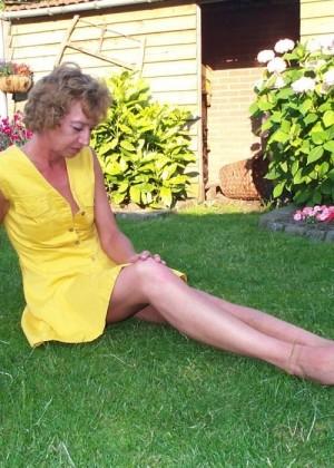 Пожилая баба лежит на травке в платье без трусов