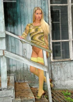 Длинноволосая блондинка в желтых чулках позирует голая на крыльце старого дома