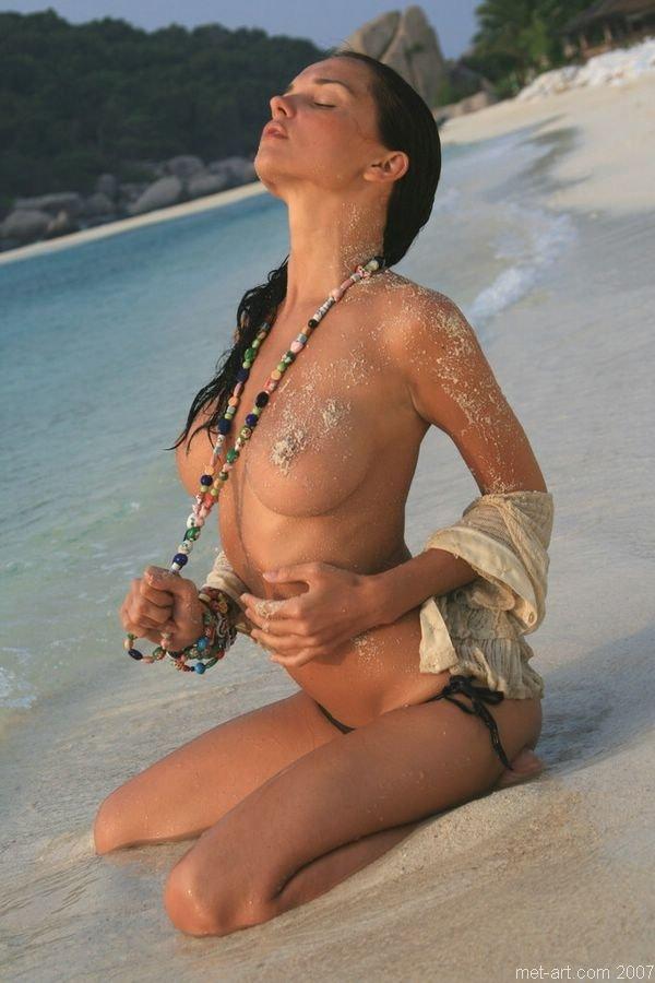 Прекрасная брюнетка обнажается на морском побережье