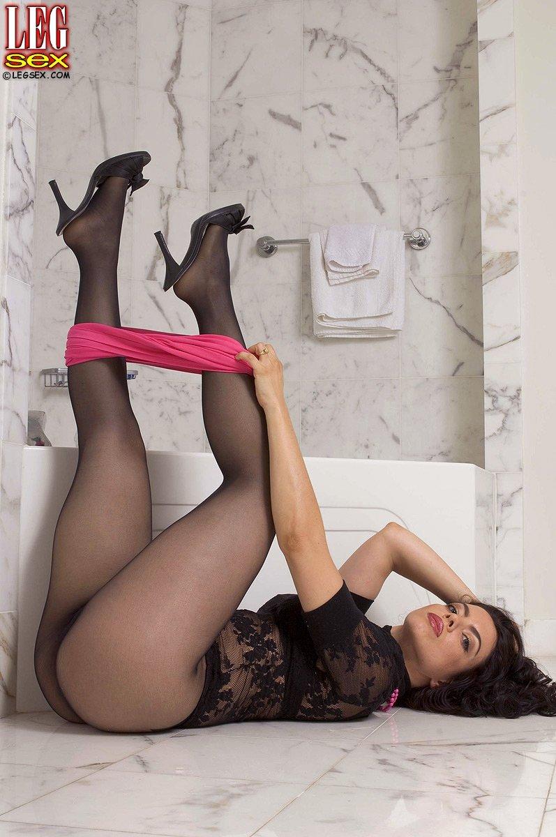 Женщина с роскошным телом в колготках без трусиков снимает юбкю