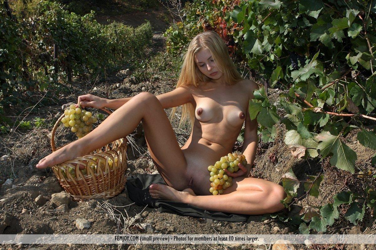 Молодая блондинка позирует голая в винограднике