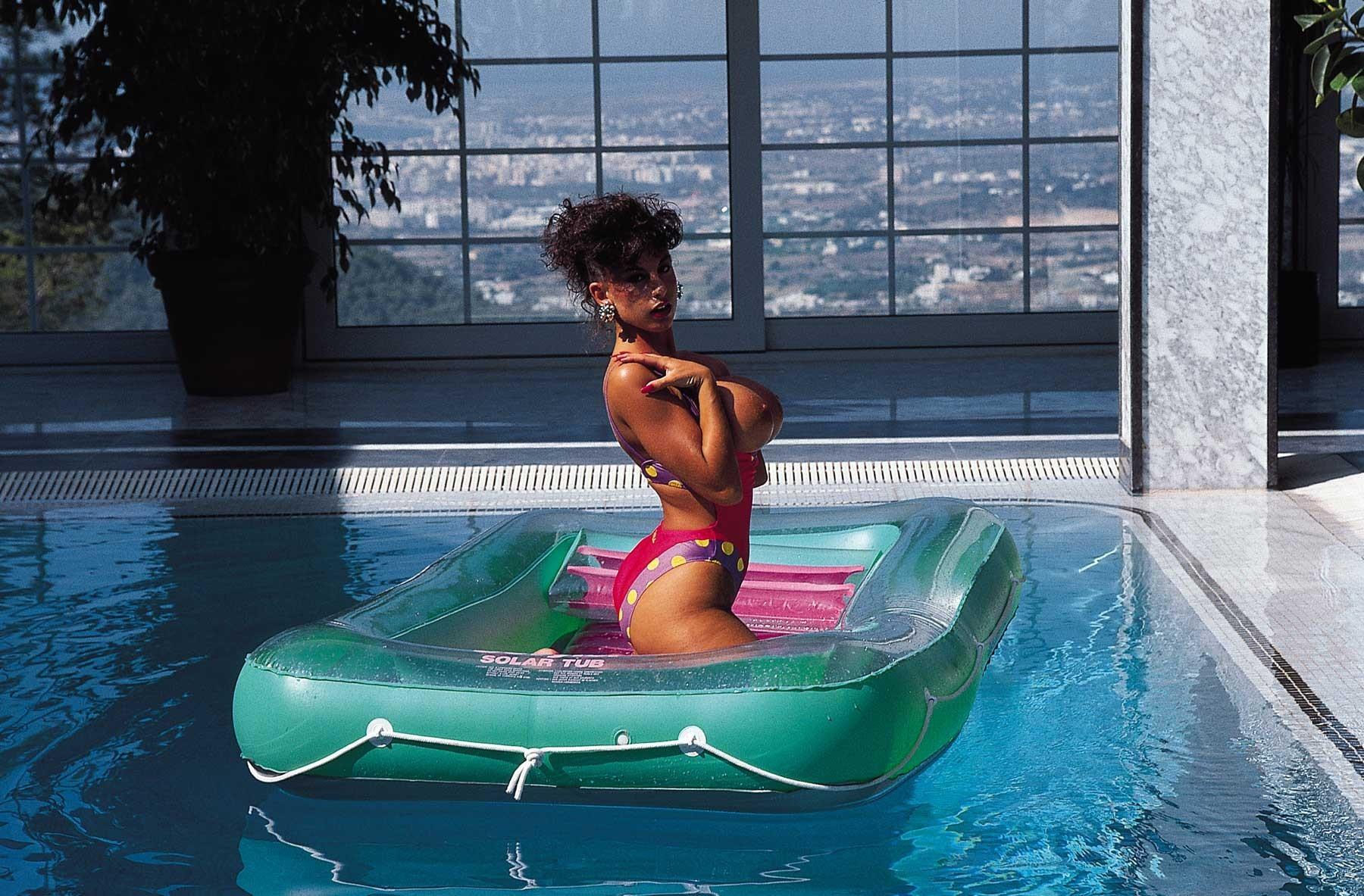 Английская модель с круглыми силиконовыми сиськами в бассейне