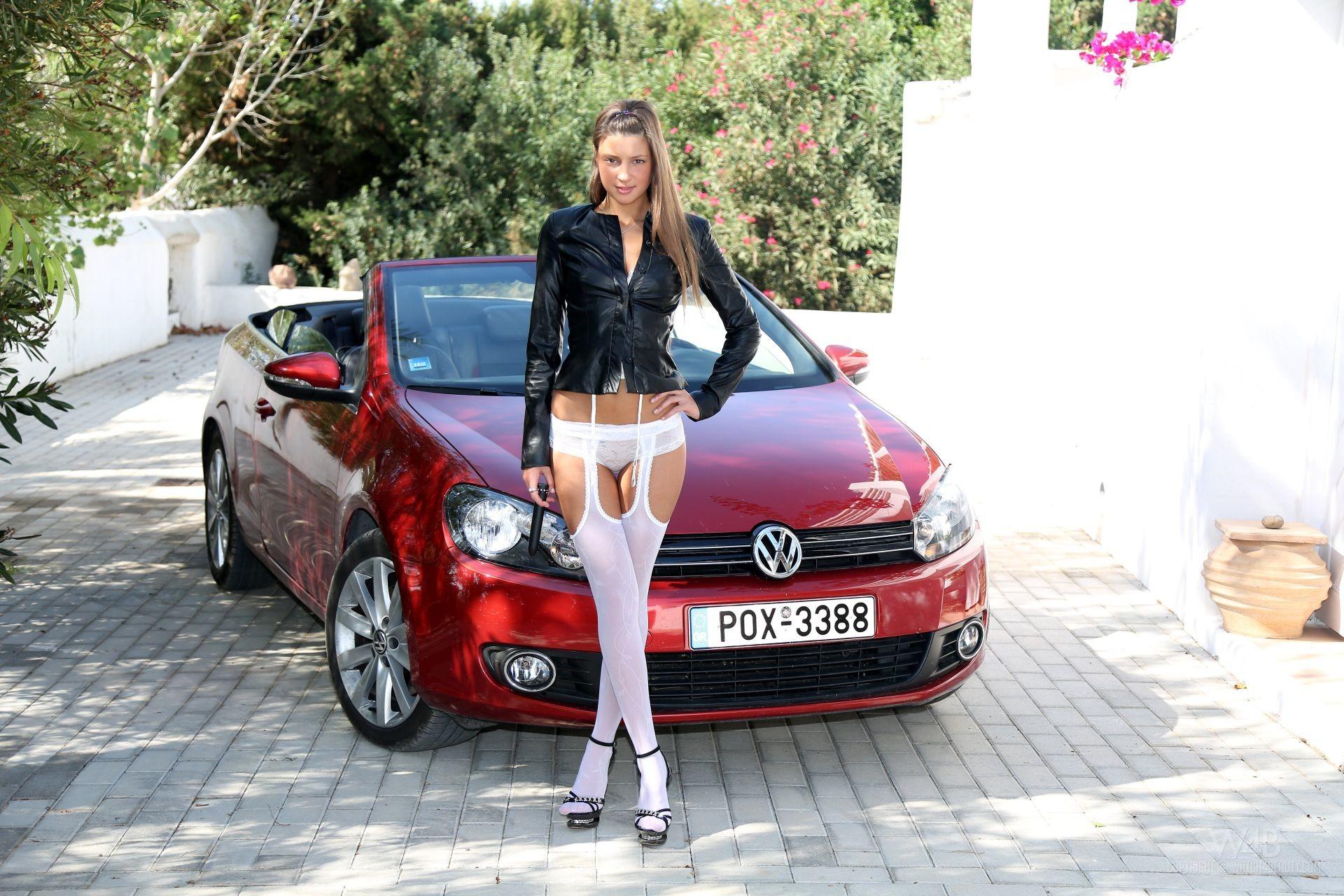Девушка с длинным языком позирует возле машины
