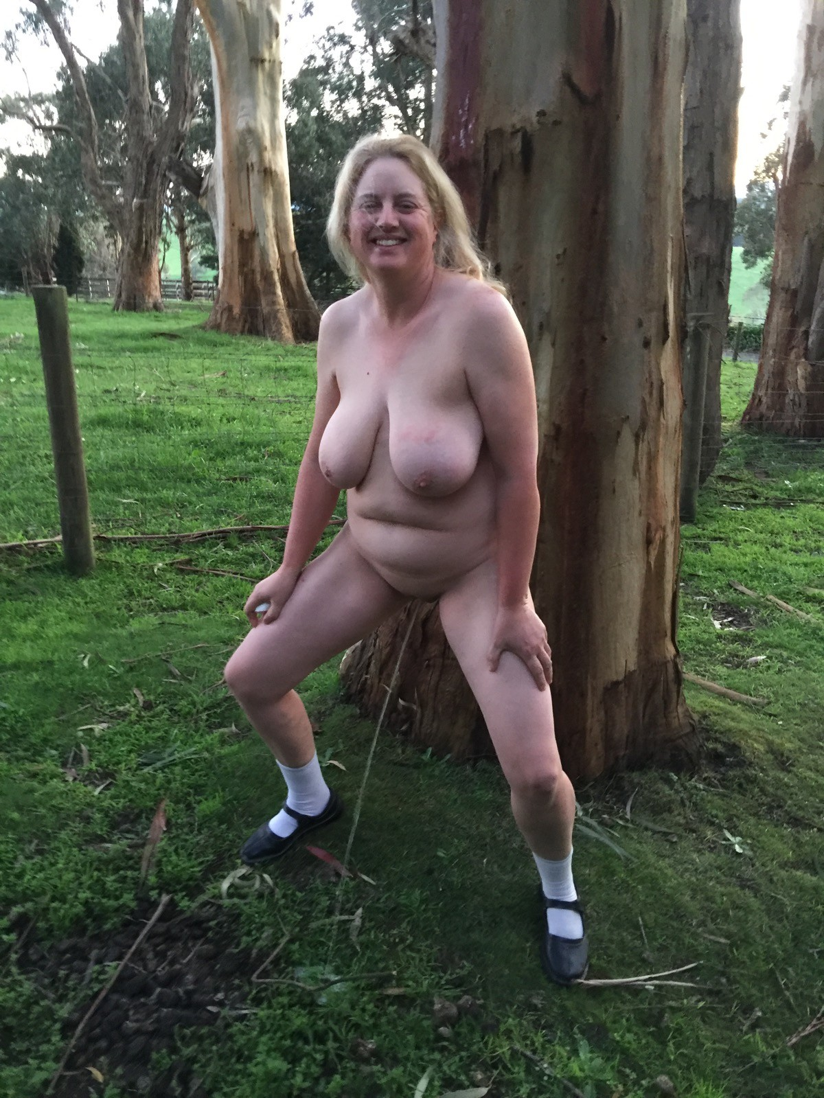 Пухлая австралийка показывает себя возле дерева