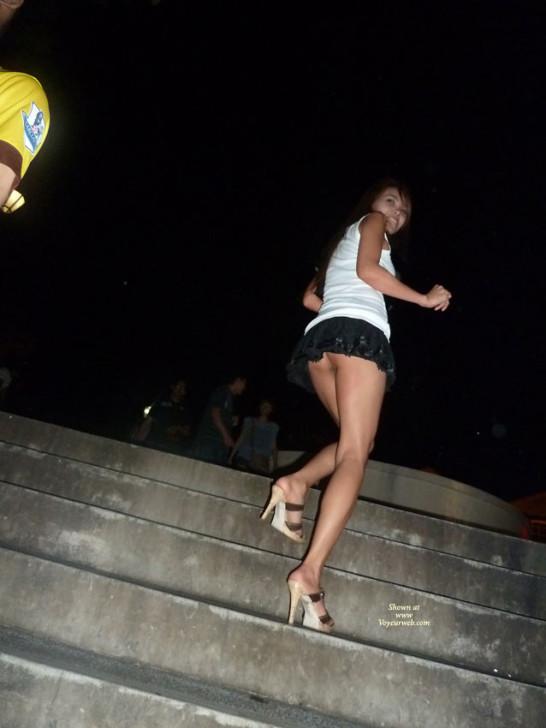 Девушка из Сингапура показывает пизду под юбкой катаясь на эскалаторе