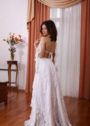 Молодая красотка снимает белоснежное платье