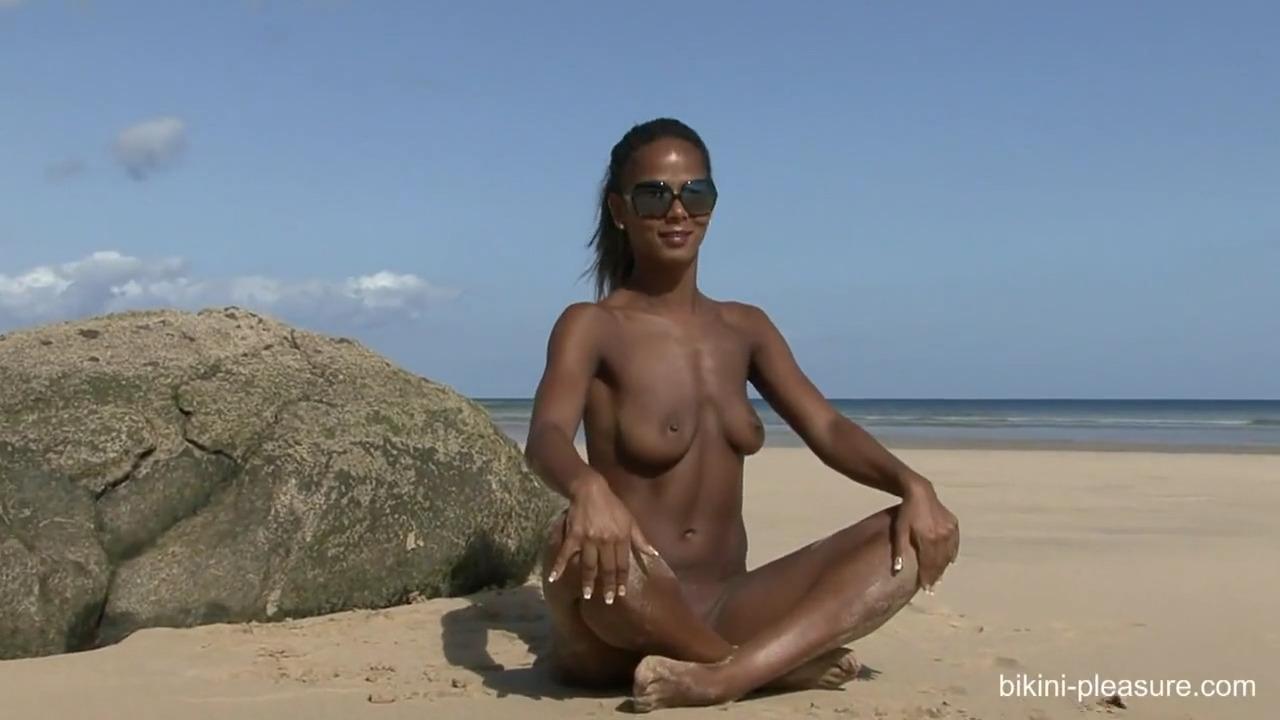Чрезмерно загорелая девушка позирует топлесс на пляже