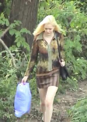 Блондинка переодевается в парке