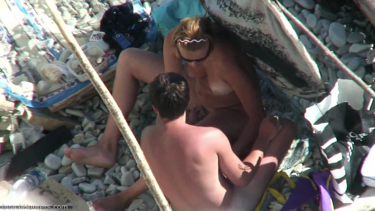 Соорудив импровизированное убежище от солнца, парочка занимается любовью на пляже